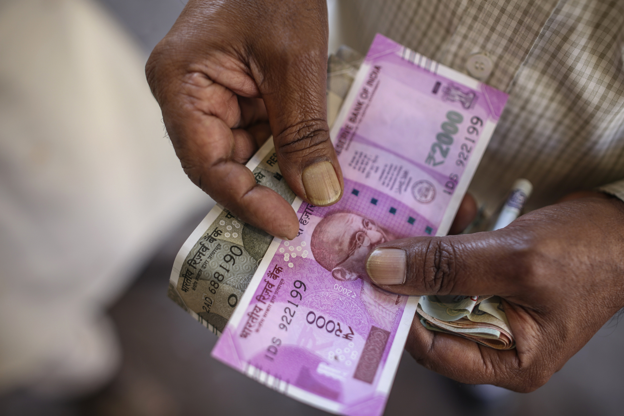 A Man Holds Two Thousand And Five Hundred Indian Ru Banknote For Photograph In Mumbai India On Friday Jan 27 2017