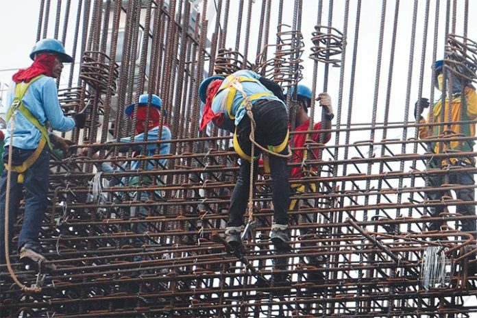 In Photo: workers install steel bars at a construction site along Aurora Boulevard in Quezon City. Strong demand from both public and private construction projects has sent the production soaring to 1 million metric tons of rebars at the largest steel maker, SteelAsia, in the first half.