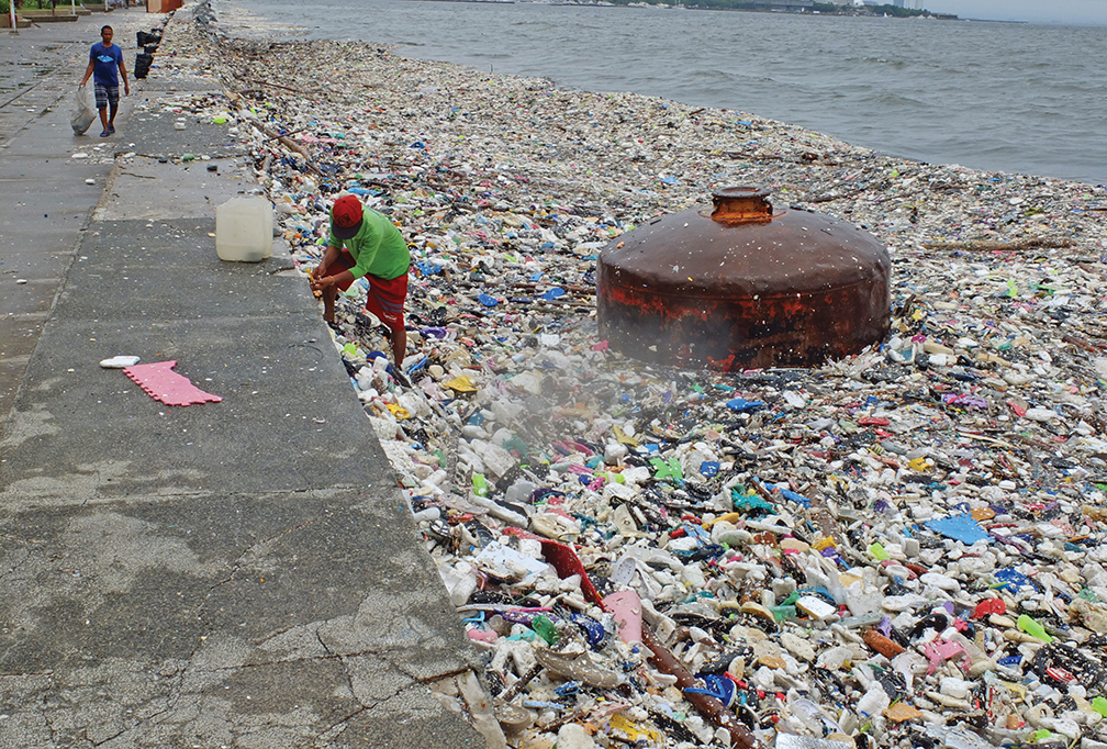 A man collects recyclable materials from the pile of garbage that was washed ashore on Manila Bay