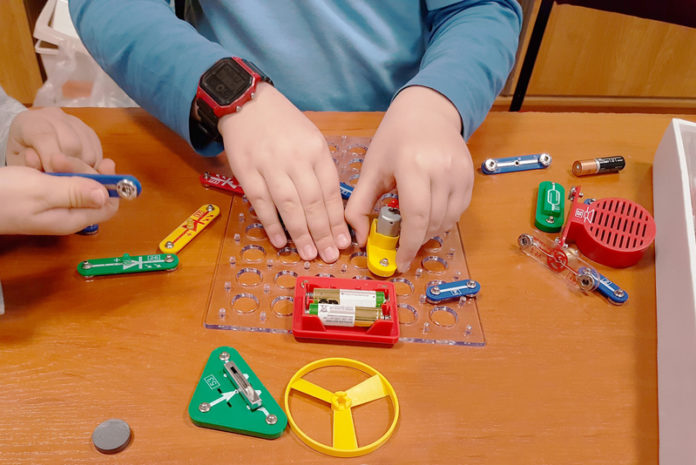 Children play an electro-mechanical constructor. Multi-colored toys for training and development of boys and girls. Physics for beginners.