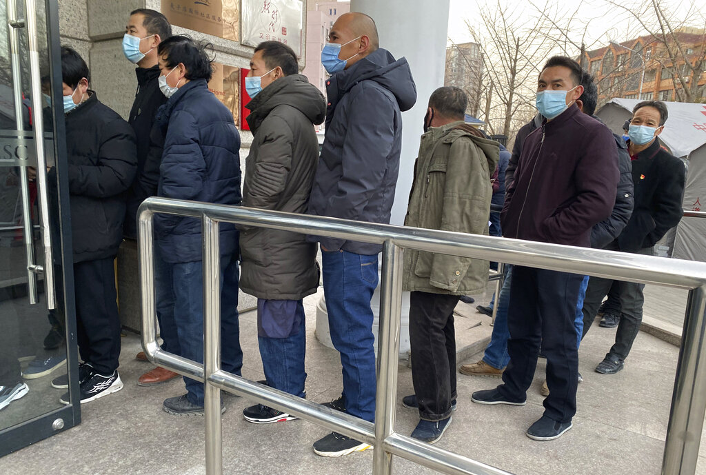 people line up for COVID-19 vaccinations in Beijing.